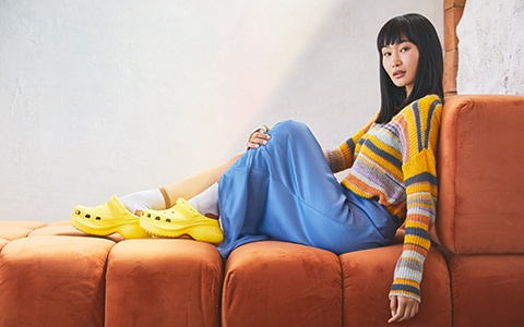 Woman posing on a sofa in the Crocs Classic Bae Clog in Sunshine.
