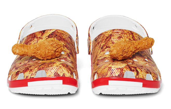 Kentucky Fried Chicken® Classic Clogs with Jibbitz™, on a pile of drumsticks.