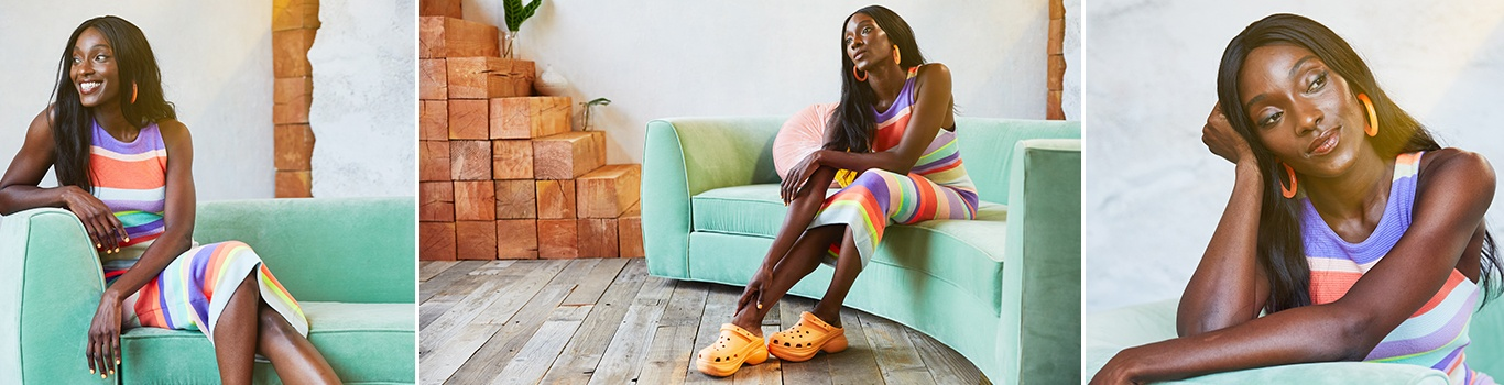 Woman posing on a sofa in the Crocs Classic Bae Clog in Cantaloupe.