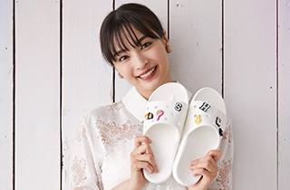 Suzu Hirose posing with the Classic Crocs Slide in White, with Jibbitz™.