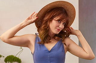 Zooey Deschanel posing in a straw hat.