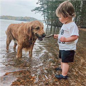 Kid in Crocs playing with dog.