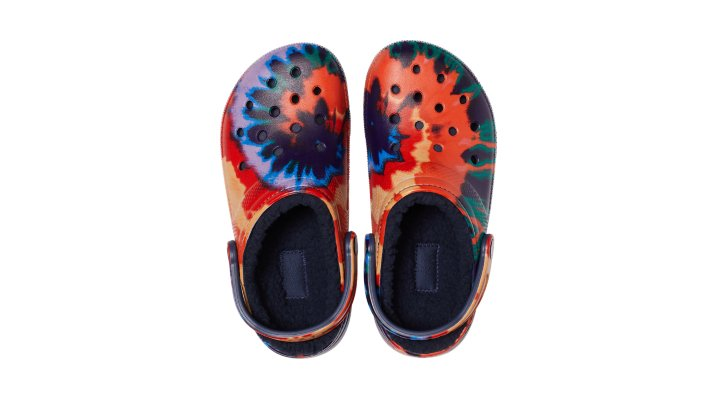 The Snuggle Is RealTimeless, fun and full of peaceful good vibes, the bright pops of tie-dye graphics on these clogs are the perfect way to make a groovy style statement on the go or while you're just hangin' out. Snuggle-ready linings are sure to inspire warm and fuzzy feelings when the temperatures drop. Grounded in comfort, spiked with personality for all ages. From downtime to downtown, these are ready to rock wherever you choose to roll.  Classic Tie-Dye Lined Clog Details:    Incredibly light and fun to wear  Pivoting heel straps for a more secure fit  Easy to clean  Customizable with Jibbitz™ charms  Dual Crocs Comfort™: Blissfully supportive. Soft. Cradling comfort.